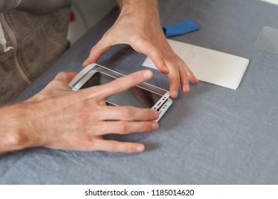 Preparing the phone to replace the screen concept. High angle top view cropped photo man is holding a new protective 3D glass over the smartphone