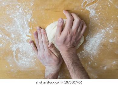 Preparing pizza dough in a kitchen.