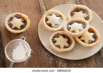 Preparing a plate of delicious Christmas mince pies decorated with pastry stars and sprinkling them with icing sugar from a sieve in a country kitchen on a wooden counter, high angle view