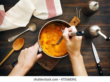 Preparing pumpkin puree. Selective focus on puree in pan