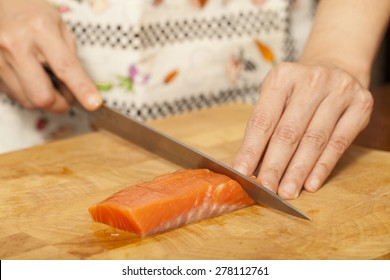 preparing salmon, an Asian woman chef preparing and carving salmon piece with sharp knife