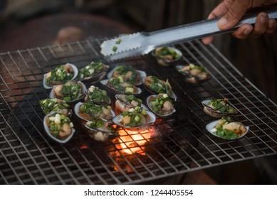Preparing seafood using open fire outdoors, Vietnam. Selective focus