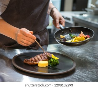Preparing to serve. Chef puts the dish on a plate.