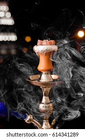 Preparing the shisha, aka nargile or hookah at a restaurant by placing the charcoals on top. A very middle eastern custom.