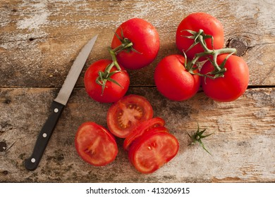 Preparing sliced ripe red tomatoes on a rustic wooden kitchen counter with a paring knife, overhead view of sliced and whole tomatoes on the vine