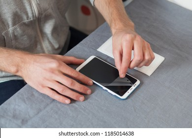 Preparing the smartphone for replacing the protective film. High angle top side profile view cropped photo of guy removes old protective glass from the digital, display phone screen