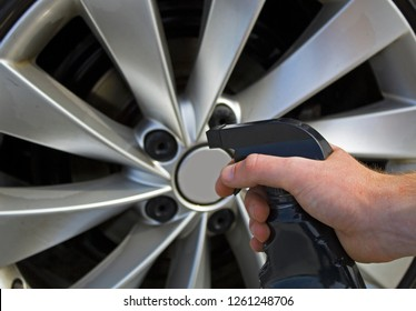 Preparing to spray car rim care product on dirty rims