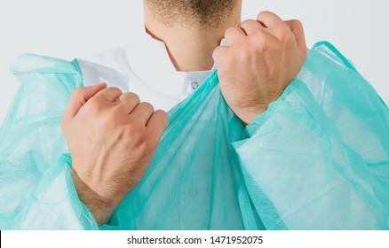 Preparing for surgery, dressing the surgeon. A man wearing a green surgical apron and a face mask on a light background. Medical and pharmaceutical concept. Saving lives.