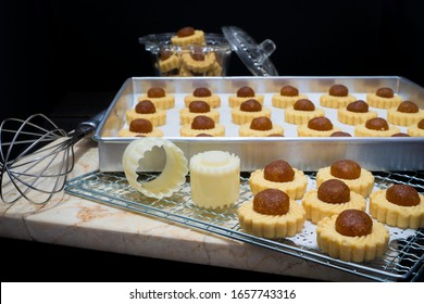 Preparing tasty pineapple tarts in a dark kitchen with the pastries cooling in a baking tray and on a wire rack alongside specialist cookie cutters, whisk and a mould