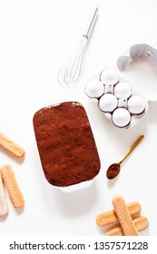 Preparing a tasty tiramisu , step by step visual guide, second lay of cream is pored followed by a sprinkle of chocolate powder as the final retouch for the perfect tiramisu cake,on a white board,