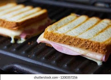 Preparing tasty toast with ham and cheese on grill