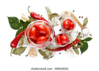 Preparing tomato preserves in glass jar on white background