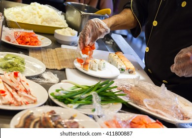 Preparing of traditional Japanese sushi rolls with salmon, hands of cook over the table with ingredients. Selective focus