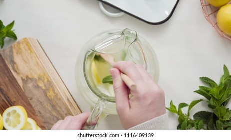 Preparing traditional lemonade with fresh sliced lemons and mint.