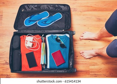 Preparing for the trip. Young man packing vacation items, mobile phone and passport.