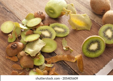 Preparing a tropical kiwifruit dessert with a high angle view of peels, peeled kiwi fruit and sliced fruit being prepared in a rustic country kitchen
