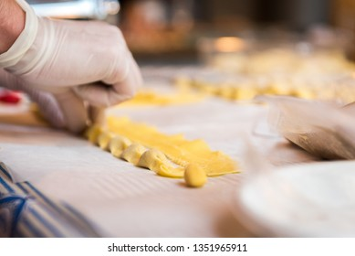 Preparing typical Italian agnolotti with fresh pasta and stew sauce on a white tablecloth