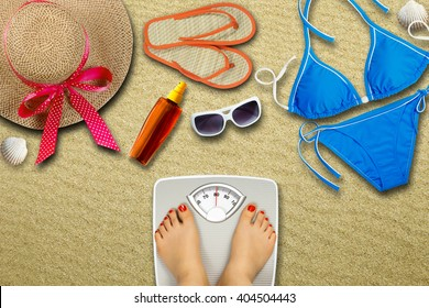 Preparing for the vacation - diet concept. Feet of a young woman on bathroom scale and summer accessories on sea sand as background