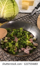 preparing a very irish dish colcannon with savoy cabbage and bacon in a pan