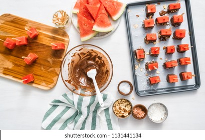 Preparing watermelon appetizers dipped in chocolate and sprinked with sea salt and almonds.