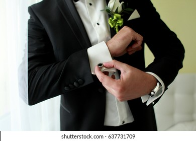 Preparing for wedding. Groom buttoning cufflinks on white shirt before wedding. True men's accessory. Groom's clothes.