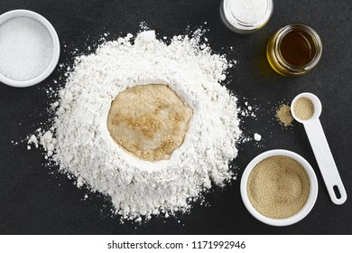 Preparing yeast dough for bread or pizza baking, photographed overhead on slate