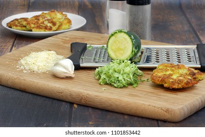 Preparing zucchini squash fritters on a cutting board with zucchini, garlic, spices, grated cheese and a grater.