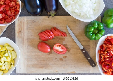 Prepping fresh vegetables for cooking in the kitchen with diced zucchini, tomato, white onion , green capsicum or bell pepper and eggplant arranged around a wooden chopping board with a knife