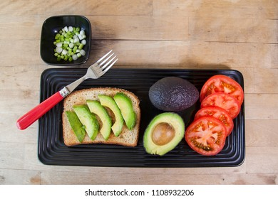 Prepping to make avocado toast with tomatoes and green onions on multigrain bread.