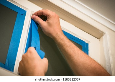 Prepping a window for painting - taping off glass with blue painter's tape.