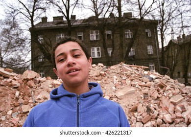 PREROV, CZECH REPUBLIC, APRIL 5, 2012: Portrait of a Gypsy young boy in the ghetto street poor Skodova,  Photographed on cine-film, photo has a characteristic color and noise, Europe