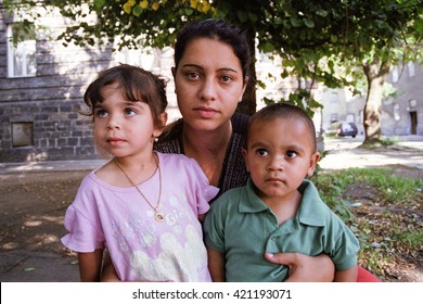 PREROV, CZECH REPUBLIC, JUNE 25, 2011: Charming and poor Gypsy family in the ghetto street Skodova, now defunct ghetto was razed. Photographed on cine-film, photo has a characteristic noise, Europe