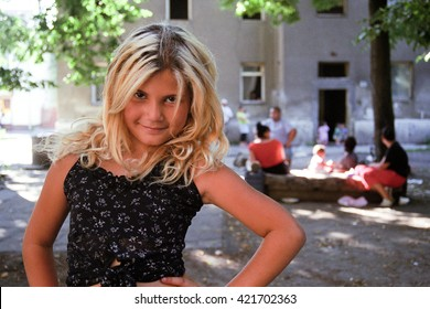 PREROV, CZECH REPUBLIC, JUNE 25, 2011: Beautiful portrait of a Gypsy young girl in the ghetto street Skodova, Photographed on cine-film, photo has a characteristic color and noise, Europe