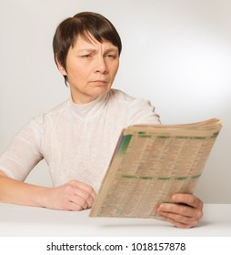 Presbyopia, vision problems. An elderly woman without glasses reads a newspaper pushing her away