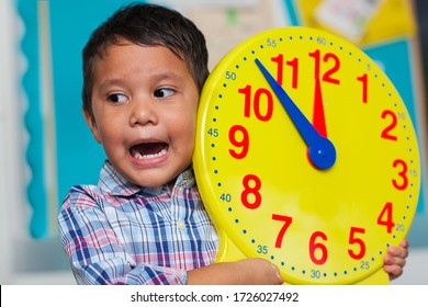Preschool age boy yelling about what time it is, while holding a big educational analog clock for kids.