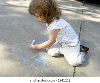 Pre-school age child drawing on sidewalk with colored chalk