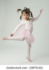 preschool age girl dancing and wearing a ballet tutu