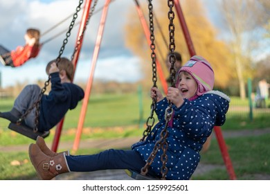 Pre-school aged caucasian female in the playground on the swing