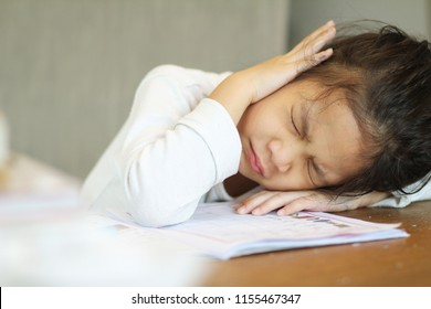 Preschool Asian little girl crying or unhappy while doing homework or  boring in her studying,don't enjoy the top or in trouble.