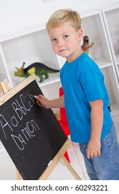 preschool boy in front of blackboard