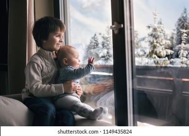Preschool boy, holding his baby brother, sitting by the window in living room, looking at a snowy landscape outdoors, winter snowing weather