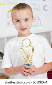 preschool boy holding a trophy in classroom
