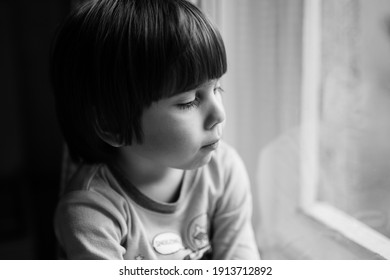 Preschool boy looking outside his home window. Authentic black and white portrait of a cute kid indoors. Candid approach with selective focus.