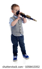 """A preschool boy """"playing"""" the wrong end of a toy clarinet.  On a white background."""