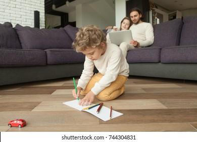 Preschool boy son drawing with colored pencils in album while parents using laptop on couch at background, creative little kid playing on living room floor, family leisure at home, child development