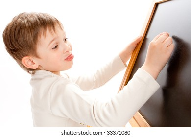 Preschool boy writing something on a  board