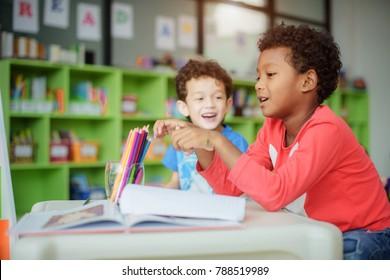 preschool boys kid playing around in drawing classroom