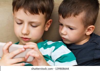 Preschool boys playing on smartphone