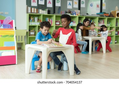 preschool boys sitting and reading together with friends and teacher in background
