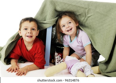 A preschool brother and sister peeking out from their play under a blanket-covered table.